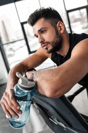 Photo pour Jeune sportif penché au tapis roulant et tenant une bouteille de sport avec de l'eau dans la salle de gym - image libre de droit