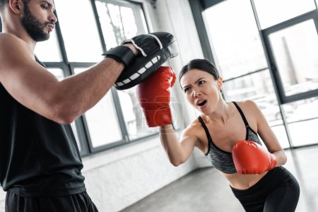Photo for Aggressive young sportswoman boxing and exercising with male trainer in gym - Royalty Free Image