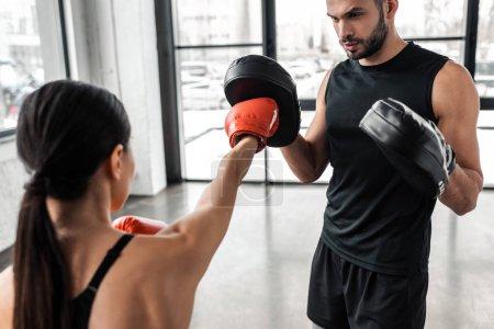 Photo pour Photo recadrée d'entraîneur masculin et jeune sportive la boxe gym - image libre de droit