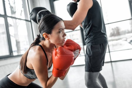 Photo for Cropped shot of concentrated sportswoman in boxing gloves exercising with trainer in gym - Royalty Free Image
