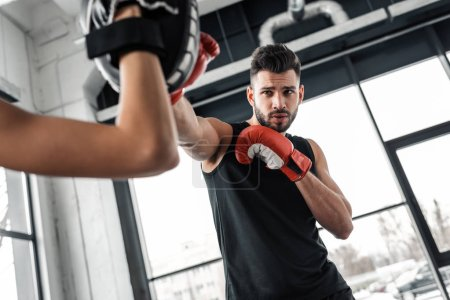 Photo for Partial view of trainer and male boxer in boxing gloves training together in gym - Royalty Free Image