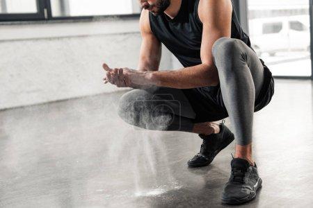 Foto de Recortado disparo de joven deportista agacharse y aplicar talco en las manos en el gimnasio - Imagen libre de derechos
