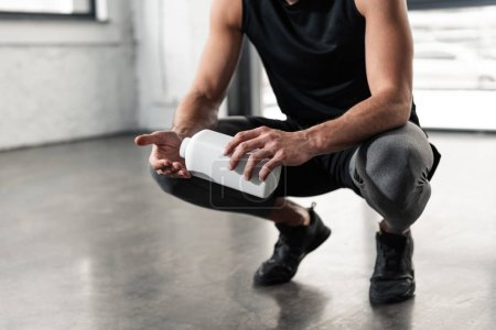 Photo for Cropped shot of sportsman holding plastic container and applying talcum powder on hands in gym - Royalty Free Image