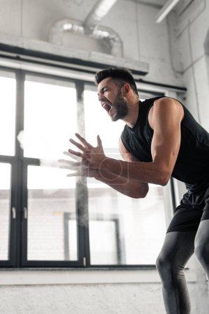 Photo pour Vue à faible angle du sportif agressif criant et appliquant de la poudre de talc sur les mains dans la salle de gym - image libre de droit