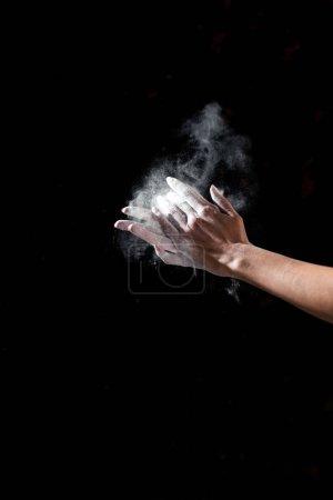 Photo pour Vue partielle de la femme appliquant de la poudre de talc sur les mains isolées sur noir - image libre de droit