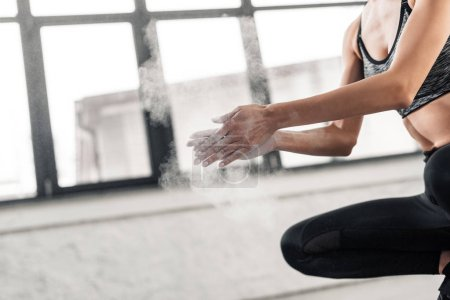 Photo for Cropped shot of young sportswoman applying talcum powder on hands in gym - Royalty Free Image