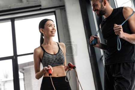 Photo for Happy sporty young couple holding jumping ropes and smiling each other in gym - Royalty Free Image