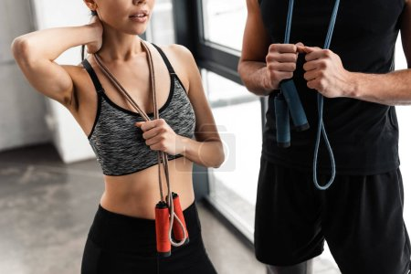 Photo for Cropped shot of young sportsman and sportswoman holding skipping ropes in gym - Royalty Free Image
