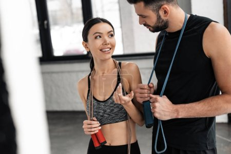 Photo for Happy sporty young couple with skipping ropes smiling each other in gym - Royalty Free Image