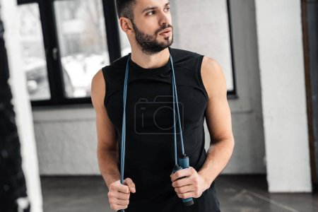 Photo for Cropped shot of handsome sportsman holding skipping rope around neck and looking away in gym - Royalty Free Image
