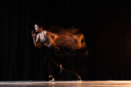 Photo for Blurred motion of athletic young woman in sportswear running on black - Royalty Free Image