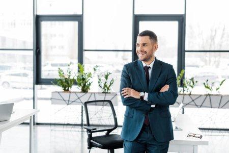 Photo pour Gai homme debout avec les bras croisés dans le bureau moderne - image libre de droit