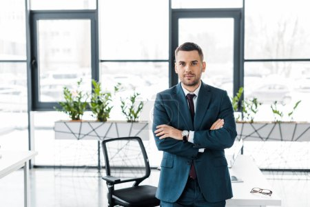 Photo for Handsome businessman standing with crossed arms in modern office - Royalty Free Image
