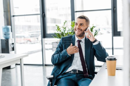 businessman smiling while talking on smartphone in modern office
