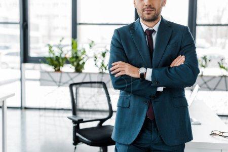 Foto de Vista recortada de hombre de negocios de pie con los brazos cruzados en la oficina moderna - Imagen libre de derechos