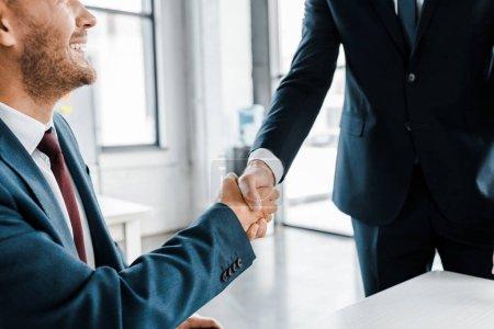 Photo pour Rogné viw d'hommes d'affaires secouer les mains dans le bureau moderne - image libre de droit