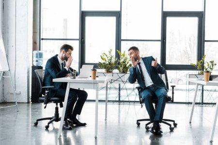 Photo for Businessmen in formal wear gossiping while sitting in modern office - Royalty Free Image