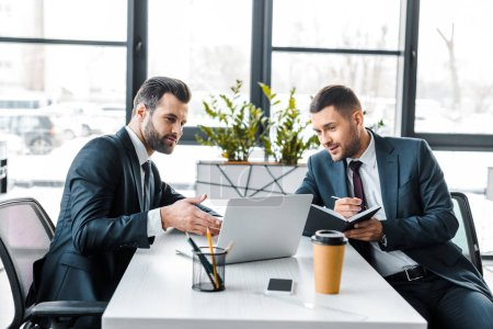 Photo for Handsome businessman talking with coworker while holding notebook and pen in hands - Royalty Free Image