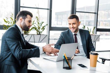 Foto de Hombre de negocios guapo mostrando algo en la computadora portátil a sonriente compañero de trabajo en la oficina moderna - Imagen libre de derechos
