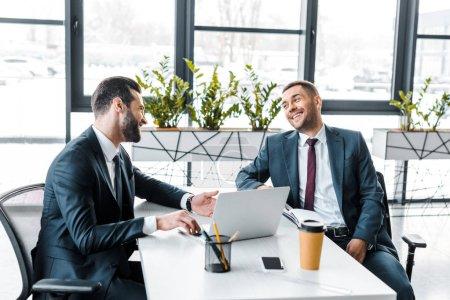 Photo pour Bel homme d'affaires collaborateur en regardant et souriant dans le bureau moderne - image libre de droit