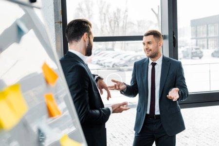 Foto de Enfoque selectivo del empresario guapo hablando con compañero de trabajo en la oficina moderna - Imagen libre de derechos