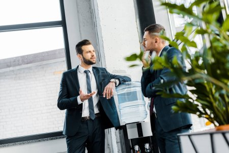 Photo for Businessman having discussion with coworker in modern office - Royalty Free Image