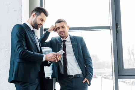 Photo for Handsome businessman looking at smartphone near colleague with hand in pocket - Royalty Free Image