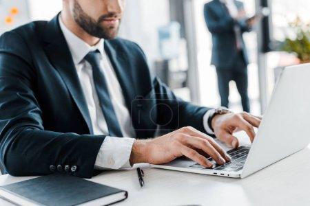 Photo pour Vue d'homme d'affaires, dactylographie sur ordinateur portable avec une collègue sur fond de rognée - image libre de droit
