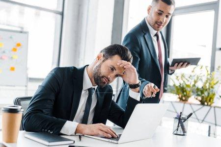 Photo pour Mise au point sélective de bel homme d'affaires à l'aide de portable proche collaborateur dans le bureau moderne - image libre de droit