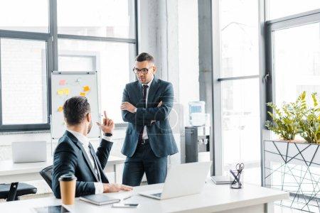 Foto de Enfoque selectivo del empresario guapo en gafas mirando a compañero de trabajo mostrando el dedo medio - Imagen libre de derechos