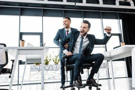Photo pour Gai homme d'affaires, à cheval sur la chaise près de collaborateur dans le bureau moderne - image libre de droit