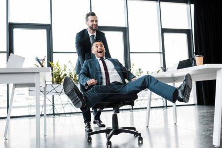 Photo pour Heureux homme d'affaires poussant chaise avec gai collaborateur dans le bureau moderne - image libre de droit