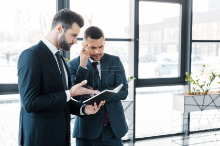 handsome businessman looking at notebook near colleague in modern office