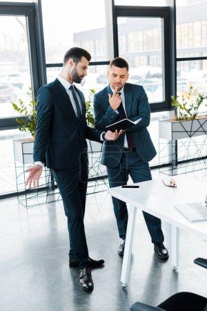 Foto de Hombre de negocios guapo sosteniendo notebook mientras está hablando con el colega en la oficina moderna - Imagen libre de derechos