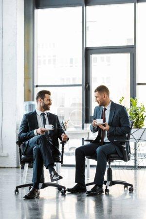 Photo pour Hommes d'affaires gais parler tout en tenant des tasses avec boissons - image libre de droit