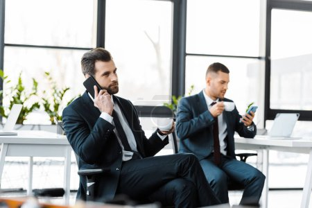Photo for Businessman talking on smartphone while holding cup with drink near colleague - Royalty Free Image