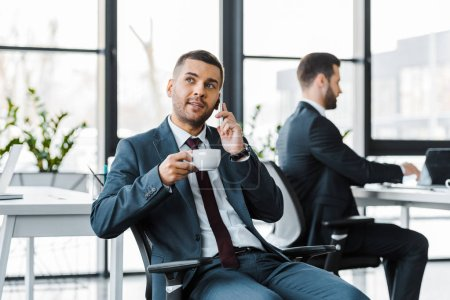 selective focus of businessman holding cup and talking on smartphone near colleague using laptop