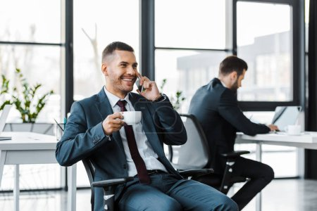 Photo for Selective focus of cheerful businessman holding cup and talking on smartphone near colleague using laptop - Royalty Free Image
