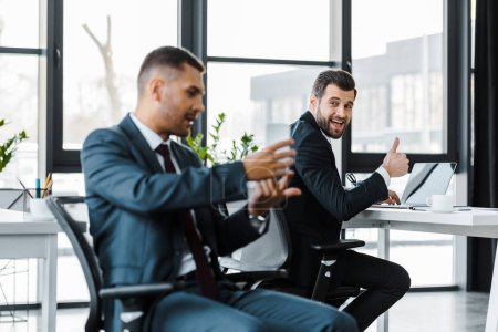 selective focus of cheerful businessman showing thumb up near colleague holding smartphone