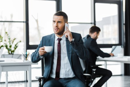 enfoque selectivo de hombre de negocios enojado sosteniendo taza con bebida y hablando en el teléfono inteligente cerca de colega
