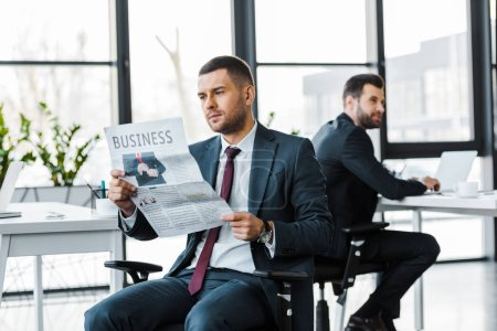 Photo for Selective focus of handsome businessman reading business newspaper near coworker - Royalty Free Image