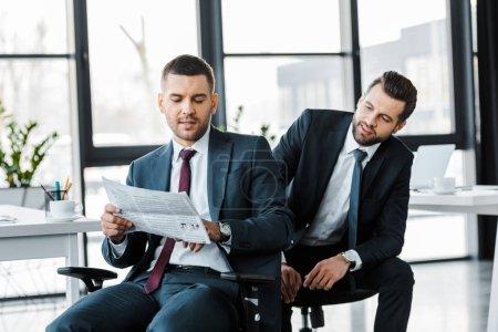 Photo pour Hommes d'affaires beau lire le journal d'affaires dans le bureau moderne - image libre de droit