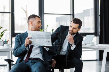 Photo pour Bel homme d'affaires assis avec collègue et lisant le journal au bureau moderne - image libre de droit