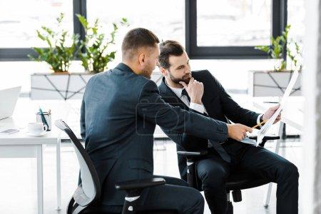 Photo pour Homme d'affaires pointant sur papier à la main sur le collaborateur dans le bureau moderne - image libre de droit