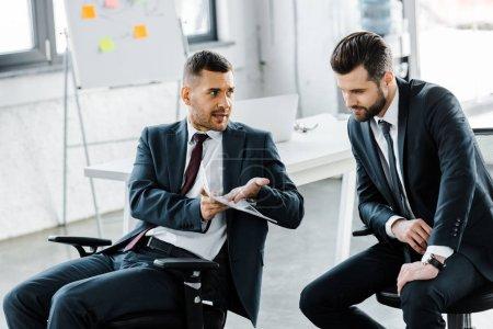 Photo pour Homme d'affaires beau parler avec collègue tout en tenant le journal au bureau moderne - image libre de droit