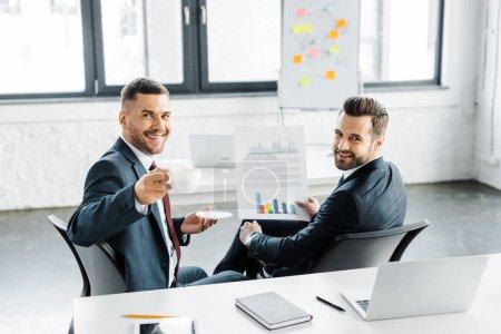 Photo pour Foyer sélectif de joyeux homme d'affaires tenant papier avec des graphiques près de collègue heureux avec tasse - image libre de droit