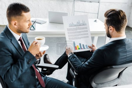 Photo for Selective focus of businessman holding paper with graphs near coworker with cup of coffee - Royalty Free Image