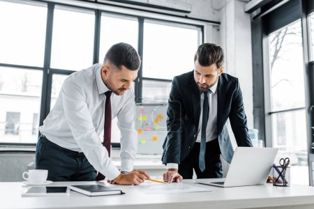 confident businessmen having discussion while standing near desk in modern office