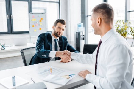 Photo for Selective focus of businessman shaking hands with coworker in modern office - Royalty Free Image