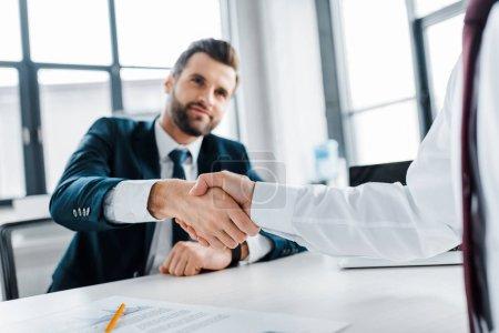 selective focus of handshake of businessmen in modern office